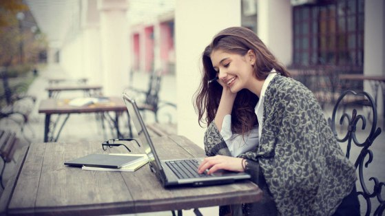 smiling-young-woman-with-laptop-outdoors